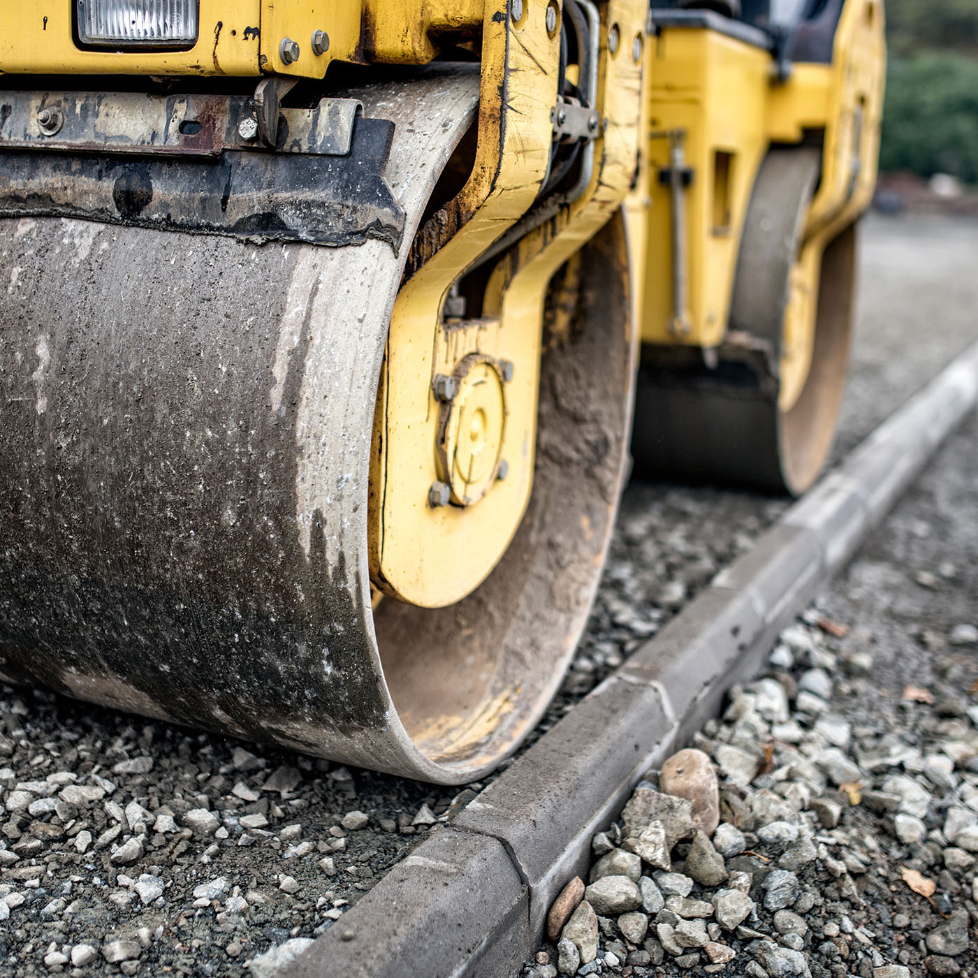 Heavy tandem road roller compacting layers of gravel on road con